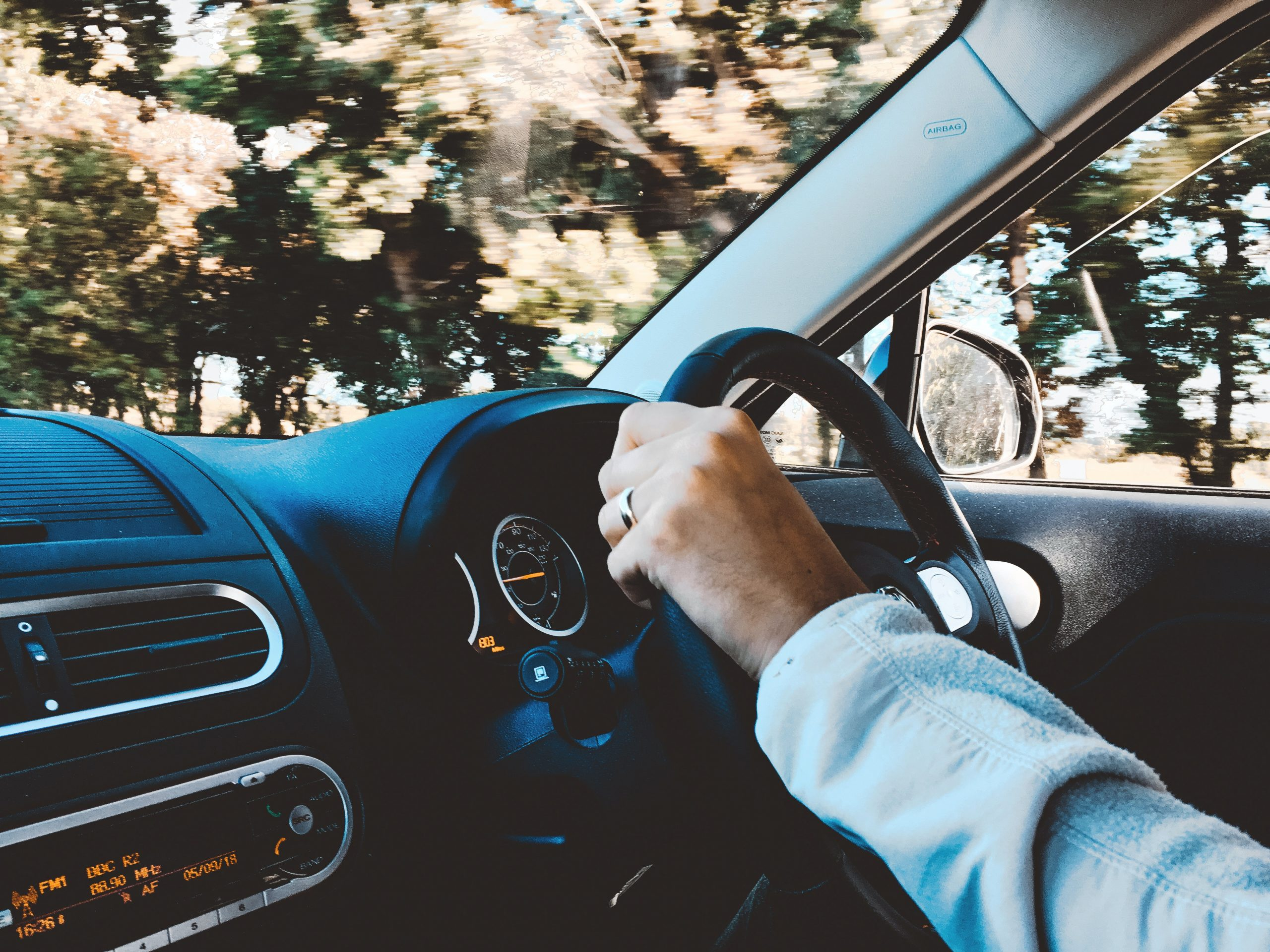 Interior of car showing person's arm on steering wheel